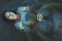 Girl is drowned under water. The girl is drowned under water. In her hands she holds a blue flowers. She is wearing a white dress stock photo