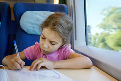 Girl drows on magazine cover, sitting in train Stock Image