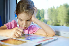 Girl drows something in magazine Stock Images