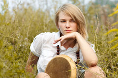 Girl with drum. Young beautiful pensive girl with drum on a field stock photos
