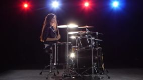 Girl drummer with chopsticks beats rhythmic music. Black background . Red light blue. Side view. Drummer girl is sitting and drum chopping beats rhythmic music stock footage