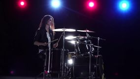 Girl drummer with chopsticks beats rhythmic music. Black background . Red light blue. Side view. Slow motion. Drummer girl is sitting and drum chopping beats stock video