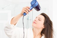 Girl drying hair in bathroom Stock Image