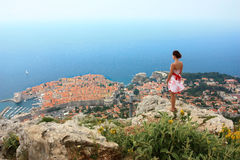 Girl in Dubrovnik. Young white woman enjoying the view over the old town of Dubrovnik with its red roofs Stock Photo