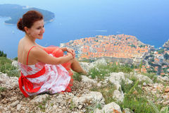 Girl in Dubrovnik. Young white woman enjoying the view over the old town of Dubrovnik with its red roofs Royalty Free Stock Photography