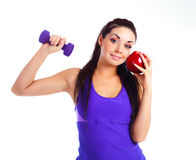 Girl with a dumbbell and an apple Royalty Free Stock Images