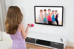 Girl With Dumbbell In Front Of Television Stock Photo