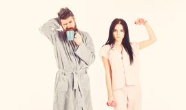 Girl with dumbbell, man with coffee cup. Couple in love in pajama, bathrobe stand isolated on white background. Couple. Girl with dumbbell, men with coffee cup royalty free stock photos