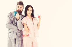 Girl with dumbbell, man with coffee cup, isolated on white background. Couple in love in pajama, bathrobe stand back to. Girl with dumbbell, men with coffee cup royalty free stock photo