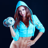 Girl with dumbbells on a black background Stock Photography