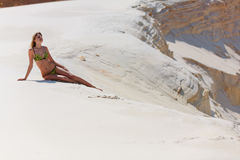 The girl in dunes from sand. The girl in a bathing suit sits in sand Royalty Free Stock Photo