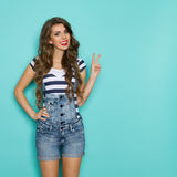 Girl In Dungarees Showing Peace Hand Sign Royalty Free Stock Photos