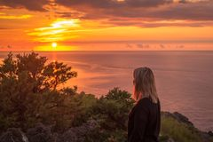A girl in dusk watching sunset. Woman watch sunset. Romantic sunset on the cliff Stock Photo