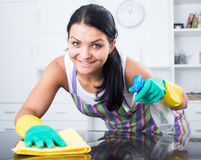 Girl dusting furniture. Young girl in apron and gloves dusting furniture Stock Photography