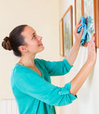 Girl dusting the picture in gallery. Happy smiling girl dusting the picture in the gallery Stock Photography