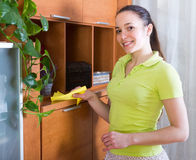Girl dusting wooden furniture at home Stock Images