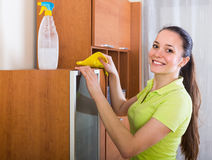 Girl dusting wooden furniture at home. Smiling girl cleaning furniture with cleanser and rag in living room Royalty Free Stock Images