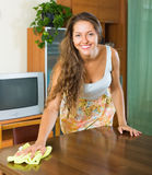 Girl dusting wooden table Stock Photography