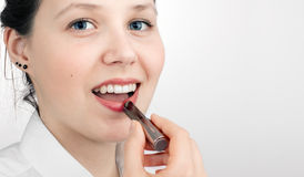Girl dyes lips by lipstick Royalty Free Stock Image