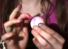Girl dying Easter eggs and her fingers royalty free stock photography
