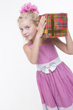 Girl is eager to open a gift. Girl is excited about a birthday gift Royalty Free Stock Image