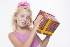Girl is eager to open a gift. Girl is excited about a birthday gift Stock Images