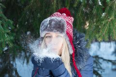 Girl in ear-flap hat blows out snow near green fir tree. Outdoor in winter day Stock Photo