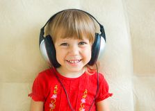 The girl in ear-phones. The cheerful girl in ear-phones listens to music royalty free stock images