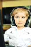 Girl  in ear-phones. Beautiful little girl  in ear-phones  listens to music Royalty Free Stock Photo