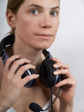 The girl in ear-phones. Portrait of the young girl in ear-phones on a white background Stock Photo