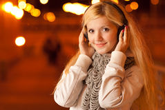 Girl in ear-phones in evening Stock Photography