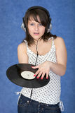 Girl in ear-phones with a phonograph record Royalty Free Stock Photos