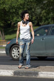 Girl with ear-phones stands on road among cars Royalty Free Stock Photography