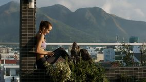 Girl in Earphone Rests on Terrace Listens to Music. Side view pretty girl puts on earphones and listens to music on modern roof terrace near pot plants stock footage