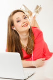 Girl with earphones and computer listening to music. Leisure free time, music, online and internet concept - happy teenage girl with earphones and laptop Stock Photo