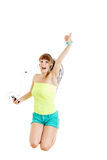 Girl with earphones jumping of joy listening to music Royalty Free Stock Photography