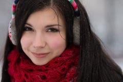 Girl in earplugs outdoors in winter Stock Photo