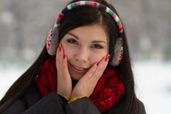 Girl in earplugs outdoors in winter Stock Photography