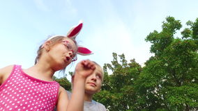 Girl with ears and glasses and boy with white hair fun talking on the background of blue sky. stock video