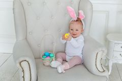 Girl in the ears of a rabbit with a basket of eggs royalty free stock image