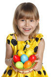 Girl with Easter basket. Little girl giving a basket with Easter eggs, high angle view, isolated on white background Stock Photo