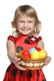Girl with Easter basket. Little girl giving a basket with Easter eggs, isolated on white background Royalty Free Stock Images