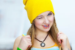 The girl with Easter candies on lips winks Royalty Free Stock Photography