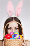 Girl with easter egg basket. Funny Brunette looking at easter egg basket Stock Photo