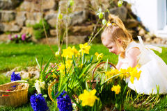 Girl on Easter egg hunt with eggs Stock Images