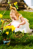 Girl on Easter egg hunt with eggs Royalty Free Stock Image