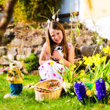 Girl on Easter egg hunt with living Easter Bunny Royalty Free Stock Photography