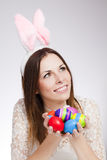 Girl with easter eggs. Brunette smiling and holding pile of easter eggs Royalty Free Stock Photo