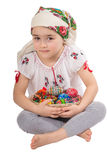 Girl with Easter Eggs. Young girl dressed in traditional costume holding a basket with Eastern eggs and hand made dolls royalty free stock photos