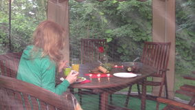 Girl eat meat alone in gazebo. Dinner table with candle, flower stock footage